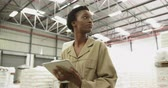 felcsavar : Low angle close up of a young African American woman using a tablet computer in a warehouse storeroom. They are working in a freight transportation and distribution warehouse. Industrial and industrial workers concept 4k