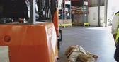 versicherung : Close up of a young Asian male warehouse worker jumping out a forklift truck to assist a colleague lying on the floor after an accident in the warehouse loading bay. They are working in a freight transportation and distribution warehouse. Industrial and i