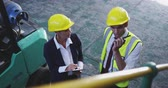 havran : Elevated close up view of middle aged Caucasian female warehouse manager and young Asian male warehouse manager wearing yellow hard hats talking in a warehouse, he is also talking on a two-way radio. They are working in a freight transportation and distri