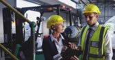 havran : Close up front view of a middle aged Caucasian female warehouse manager and a young Asian male warehouse manager talking in a warehouse loading bay. She is making notes on a clipboard. They are both wearing yellow hard hats. They are working in a freight