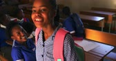 township : Portrait close up of a young African schoolgirl wearing her school uniform and schoolbag, talking to a friend and turning to camera smiling and laughing, at a township elementary school with classmates sitting at desks in the background 4k Stock Footage