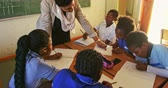 бедность : Front view close up of a middle aged African female school teacher standing at the front of the class leaning on her pupils desks while she helps them with their work during a lesson in a township elementary school classroom 4k