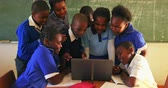 aufmerksam : Front view of a group of young African schoolchildren standing and sitting in front of the blackboard gathered around a laptop computer during a lesson in a township elementary school classroom 4k