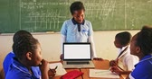 бедность : Front view of a young African schoolboy standing in front of the blackboard showing his classmates a laptop during a lesson in a township elementary school classroom. In the foreground his classmates are sitting at desks listening 4k