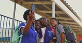 бедность : Front view close up of a group of young African schoolgirls having fun posing and taking selfies with a smartphone in a township elementary school playground 4k