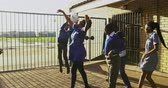 pobre : Slow motion front view of a group of young African schoolgirls and schoolboys jumping and playing with a ball by a fence in the playground at a township elementary school 4k