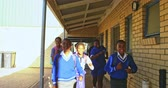 schultasche : Front view close up of young African schoolcboys and schoolgirls running in the school yard in the sun carrying schoolbags at a township elementary school 4k Stock Footage