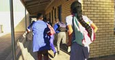 бедность : Back view close up of young African schoolcboys and schoolgirls running in the sun in the school yard carrying schoolbags at a township elementary school 4k