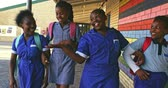 pobre : Front view of four young African schoolgirls wearing schoolbags smiling and walking with arms linked and high fiving in the playground of a township elementary school 4k
