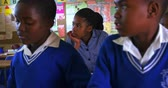 бедность : Front view close up of a two young African schoolboys and a schoolgirl listening to instructions and writing in their notebooks during a lesson in a township elementary school classroom 4k