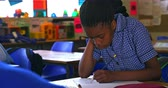 aufmerksam : Front view close up of a young African schoolgirl writing in her notebook during a lesson in a township elementary school classroom 4k Stock Footage