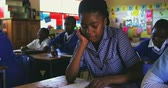 бедность : Front view close up of a young African schoolgirl writing in her notebook during a lesson in a township elementary school classroom, in the background her classmates are also writing in their books 4k Стоковые видеозаписи