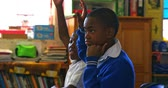 бедность : Side view close up of two young African schoolboys sitting at their desks raising their hands to answer a question during a lesson in a township elementary school classroom 4k Стоковые видеозаписи