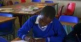 бедность : Front view close up of a young African schoolboy writing in his notebooks during a lesson in a township elementary school classroom 4k