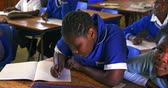бедность : Front view close up of a young African schoolgirl writing in her notebook during a lesson in a township elementary school classroom, in the background her classmates are raise their hands to answer a question 4k