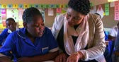 бедность : Close up front view of a middle aged African female school teacher squatting down and helping a young African schoolgirl sitting at her desk during a lesson in a township elementary school classroom, while in the background classmates are busy reading and