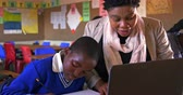 бедность : Front view close up of a middle aged African female school teacher helping a young African schoolboy sitting at his desk using a laptop computer during a lesson in a township elementary school classroom, while in the background classmates are busy working