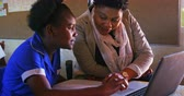 бедность : Front view close up of a middle aged African female school teacher helping a young African schoolgirl sitting at her desk using a laptop computer during a lesson in a township elementary school classroom, while beside her and in the background classmates