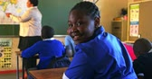 pobre : Side view close up of a young African schoolgirl sitting at his desk and turning around, looking to camera and smiling during a lesson in a township elementary school classroom. In the background the rear view of his classmates listening to the teacher st Stock Footage