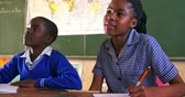pobre : Front view close up of a young African schoolgirl and schoolboy sitting at desks smiling, writing in her note book and listening attentively during a lesson in a township elementary school classroom 4k