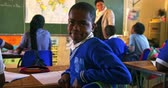 pobre : Side view close up of a young African schoolboy sitting at his desk and turning around, looking to camera and smiling during a lesson in a township elementary school classroom. In the background the rear view of his classmates listening to the teacher sta