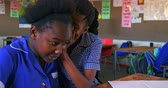 бедность : Side view close up of two young young African schoolgirls sitting at their desk whispering to each other during a lesson in a township elementary school classroom. In the background their classmates are listening to the teacher 4k