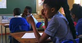 бедность : Side view close up of an upset young African schoolgirl sitting at her desk looking down and crying during a lesson in a township elementary school classroom. Beside her and in the background the rear view of her classmates writing in their notebooks 4k Стоковые видеозаписи