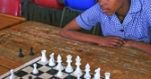 pobre : Elevated view of two young African schoolgirls sitting at a desk playing chess during a break from lessons in a township elementary school classroom 4k