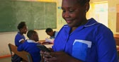 okula geri : Side view close up of a young African schoolgirl sitting at her desk using a smartphone and smiling in a classroom at a township elementary school. In the background classmates are sitting at their desks working 4k