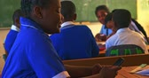 aufmerksam : Side view close up of a young African schoolgirl sitting at her desk using a smartphone and smiling in a classroom at a township elementary school. In the background classmates are sitting at their desks working 4k