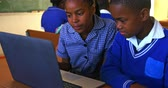 бедность : Front view close up of a young African schoolboy and schoolgirl sitting at a desk using a laptop computer together during a lesson in a township elementary school classroom, in the background classmates are sitting at their desks working 4k Стоковые видеозаписи