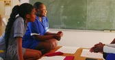 south american : Side view close up of a group of young African schoolgirls having fun and talking during a break from lessons in a township elementary school classroom 4k