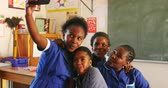 бедность : Front view close up of a group of young African schoolgirls having fun posing and taking selfies with a smartphone during a break from lessons in a township elementary school classroom 4k Стоковые видеозаписи