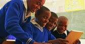 pausa : Side view close up of four young African schoolboys sitting and looking at a tablet computer during a break from lessons in a township elementary school classroom 4k Filmati Stock
