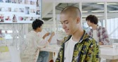 ajans : Side view close up of a young mixed race male creative professional with a shaved head turning and smiling to camera in a modern open plan office, with colleagues talking together in the background