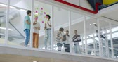 rozmowa : Front view of a group of diverse creative professionals standing at a casual meeting and writing and discussing notes on a glass wall in a modern office, seen through glass wall Wideo