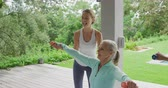 formazione personale : Front view side up of a senior Caucasian woman exercising with dumbbells in a garden, with a young Caucasian female fitness instructor, with a swimming pool behind her