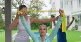 aktive senioren : Front view of a senior Caucasian woman and man exercising with rubber bands in a garden, with a young Caucasian female fitness instructor