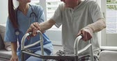 retreat : Front view close up of a senior Caucasian man using a walking frame and young Caucasian female doctor in a hospital Stock Footage