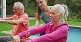formazione personale : Side view close up of a senior Caucasian woman and man exercising with dumbbells in a garden, with a young Caucasian female fitness instructor and swimming pool behind them