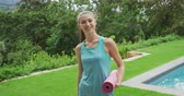 yogamatte : Portrait of a young Caucasian woman wearing sports clothes and holding a yoga mat in a garden, smiling to camera