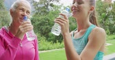 retiro : Front view close up of a senior Caucasian woman a young Caucasian female fitness instructor drinking water during a break in exercising in a garden