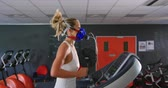 ginásio : Side view of a young Caucasian woman running on a treadmill and using a metabolic gas analyser during training, wearing a face mask