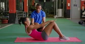 duas pessoas : Side view of a young mixed race woman exercising in a gym with a young mixed race male personal trainer, doing crunches