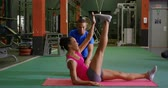 formazione personale : Side view of a young mixed race woman exercising in a gym with a young mixed race male personal trainer, doing crunches