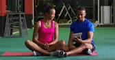motivatie : Front view of a young mixed race woman exercising in a gym with a young mixed race male personal trainer, using a tablet computer