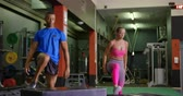 duas pessoas : Front view of a young mixed race man and a young Caucasian woman exercising in a gym, jumping on a cube