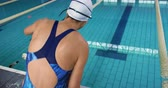 generation z : Rear view close up of a young mixed race female swimmer by a swimming pool
