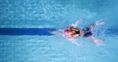 挑戦 : Overhead view of a young female swimmer training in a swimming pool, breaststroke