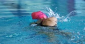 rastejando : Rear view of a young Caucasian female swimmer training in a swimming pool, crawl